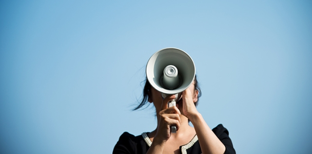 Businesswoman shouting through the megaphone in the open air.